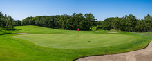 Panorama View Of Golf Course With Beautiful Putting Green. Golf Course With A Rich Green Turf Beautiful Scenery.