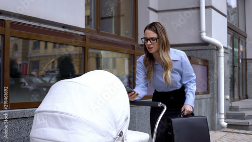 Obraz Busy mother in suit pushing baby carriage answering phone and calming baby - fototapety do salonu