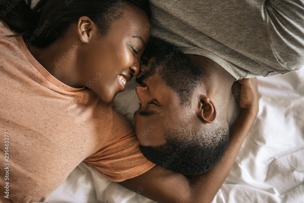 Fototapeta Loving young African American couple lying in bed together