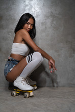 Young Beautiful Asian Girl In Retro Quads Roller Skates Posing In Studio Over Concrete Wall Background