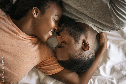 Stampa su Tela  Loving young African American couple lying in bed together
