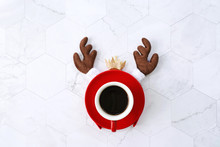 Flat Lay Of Black Coffee Red Cup With Reindeer Headband For Christmas Celebration On White Marble Background, Holiday Concept