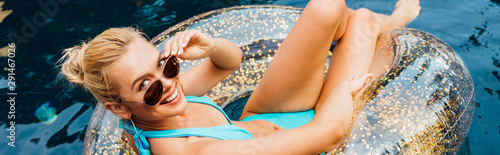 Fotografie, Obraz panoramic shot of smiling sexy young woman in swimsuit and sunglasses lying on s