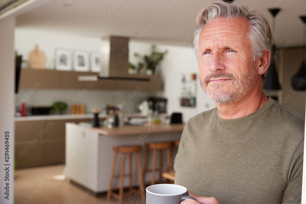 Fototapeta Senior Man Standing And Looking Out Of Kitchen Door Drinking Coffee