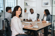 Smiling young businesswoman sitting with coworkers during a meeting
