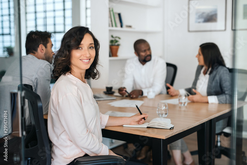 Fototapety, obrazy: Smiling young businesswoman sitting with coworkers during a meeting