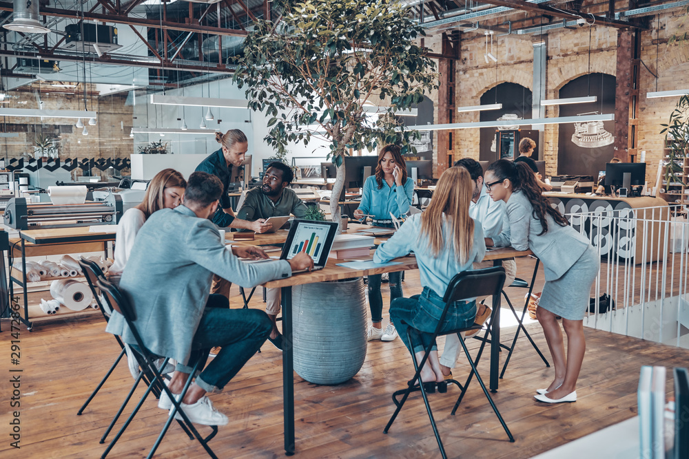 Fototapeta Group of young modern people in smart casual wear communicating and using modern technologies while working in the office