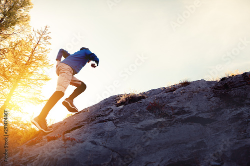 Obraz na plátně Man runs uphill on big rock at sunset