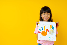 Portrait Of Young Asian Girl With Art, Thai Kid Show Painting Paper By Water Color With Palm And Creativity  Of Children Concept On Yellow Background