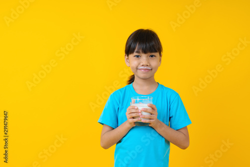 Happy Thai kid holding glass of milk isolated, young Asian girl drinking milk for strong health on yellow background