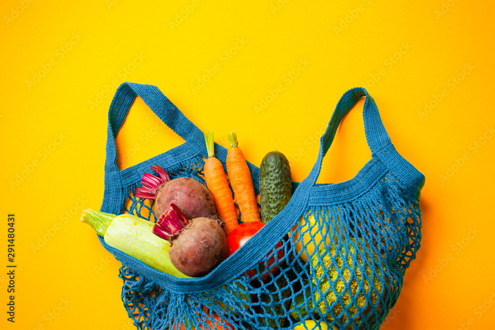 Fototapety, obrazy: Vegetables in mesh cotton bag on yellow background