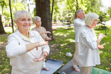 Smiling Old Lady Visiting Qigong Class In The Park
