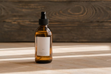 One Cosmetic Dark Amber Glass Bottle With White Lable On Wooden Table. Closeup, Copyspace. Beauty Blogging, Salon Treatment Concept, Minimalism Brand Packaging Mock Up