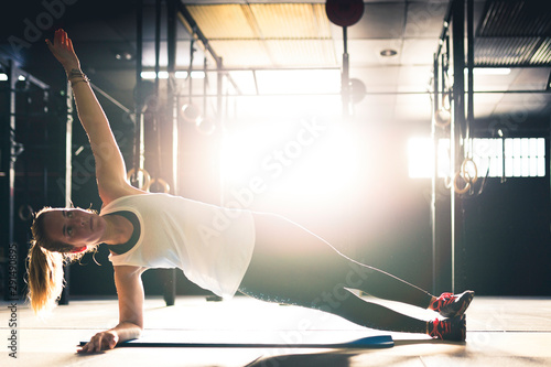 Fotografie, Tablou A blonde woman doing exercises at a gym