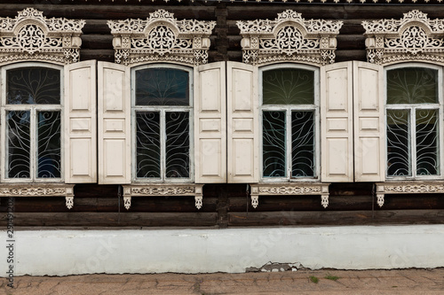 Window with the wooden carved architrave in the old wooden house in the old Russian town Wallpaper Mural