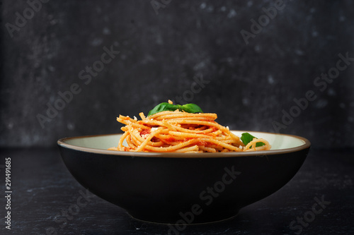 Fotomural  A plate with pasta in tomato sauce on black background