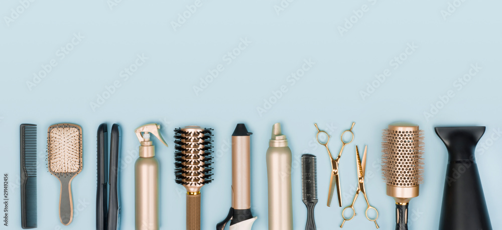 Fototapety, obrazy: Hair stylist tools arranged in a line on blue background