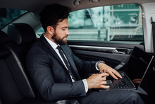 Handsome, Bearded, Smiling Top Manager In Black Suit Working On His Laptop On The Backseat Of The Car.