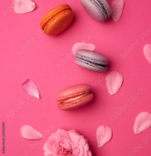 Fotobehang Macarons sweet multi-colored macarons with cream and a pink rose bud with scattered petals