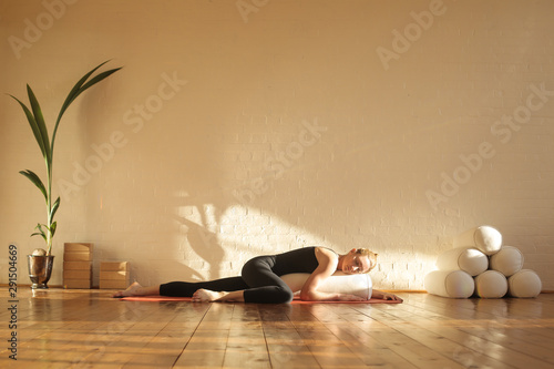 Obraz Woman practiving restorative yoga in a beautiful studio - fototapety do salonu