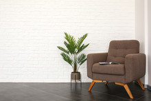 Stylish Armchair With Tropical Plant Near White Brick Wall In Room