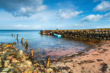 A Small Boat Moored At An Old Stone Jetty At Sannox