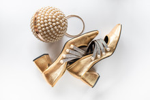 Close-up Of Gold Shoes And A Gold Clutch With Pearls On A White Background