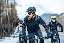 Front View Of Group Of Mountain Bikers Riding On Road Outdoors In Winter.