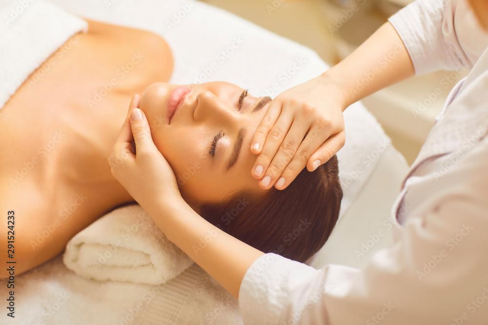Fototapeta Facial massage to a beautiful girl in a beauty clinic.