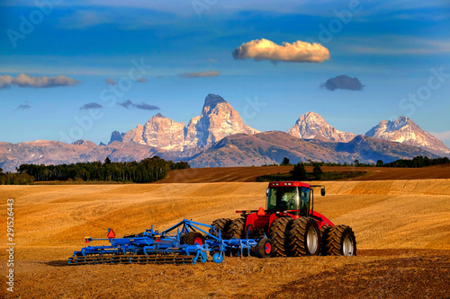 Tractor Farming Ground Harvesting Crops in Fall Autumn Teton Mountains Rugged