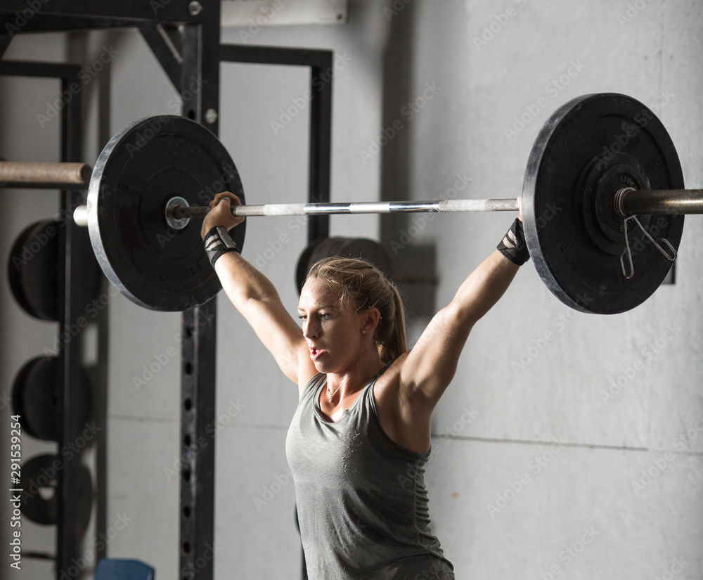 Fototapety, obrazy: Close up of strong young woman lifting barbell over her head in gym.