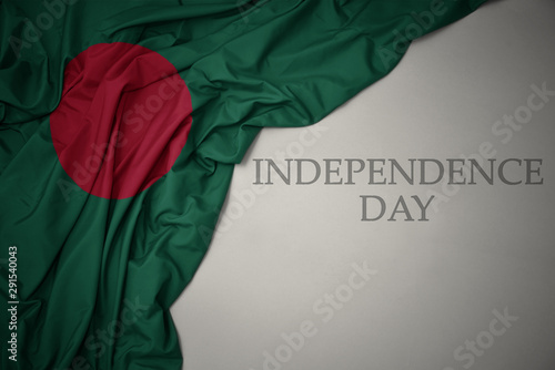 Leinwand Poster waving colorful national flag of bangladesh on a gray background with text independence day