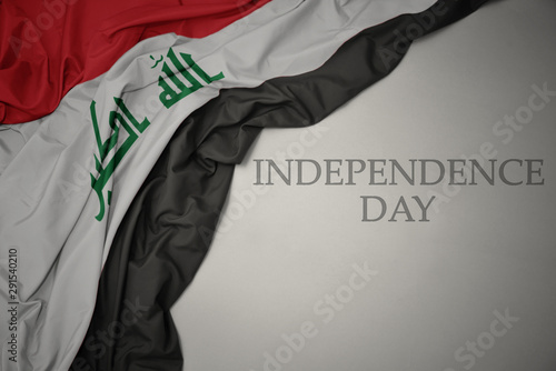 waving colorful national flag of iraq on a gray background with text independence day Tablou Canvas