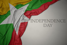 Waving Colorful National Flag Of Myanmar On A Gray Background With Text Independence Day.