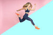 canvas print picture - Beautiful young blond hair athlete woman is running and smiling jumping in the air in motion dressed in sportswear in two colors isolated background