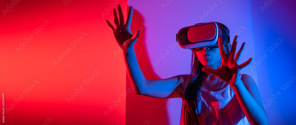 Fototapeta Young woman using glasses of virtual reality on dark background. Smartphone using with VR headset,virtual reality,future technology concept.Asian woman using VR glasses in colorful neon lights.