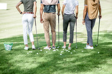 Friends Standing Together With Golf Equipment And Balls On The Green Grass, Cropped Image With No Face