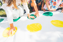 Children Play A Twister On The Grass. Hands On Yellow. Team Game