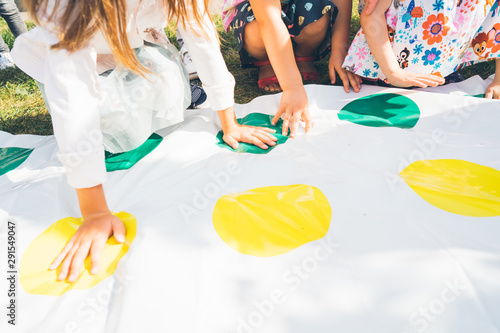 Fotografia, Obraz Children play a twister on the grass. Hands on yellow. Team game