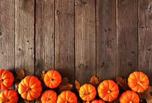 Autumn Bottom Border Of Pumpkins And Fall Leaves. Above View On A Rustic Wood Background With Copy Space.