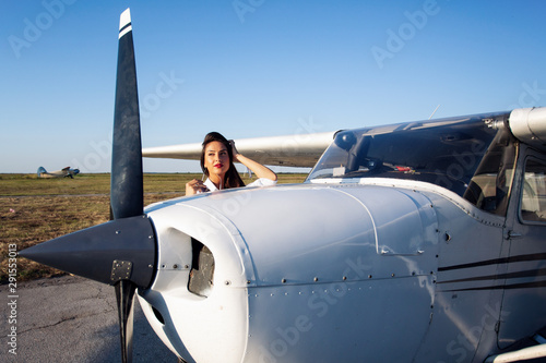 Beautiful woman standing next to a small airplane. Canvas Print