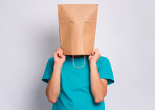 Portrait Of Teen Boy With Paper Bag Over Head. Teenager Cover Head With Bag Holding Hand Near Face Posing In Studio. Child Pulling Paper Bag Over Head.