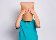 Portrait Of Teen Boy With Paper Bag Over Head With Hands On Face Covering Eyes. Teenager Cover Head With Bag Close Eyes With Palms Posing In Studio. Child Pulling Bag Over Head. See No Evil Concept.