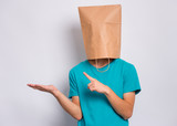 Teen boy with paper bag over head pointing finger away at copyspace, isolated on white background. Teenager cover head with shopping bag pointing finger at something. Child pulling paper bag over head