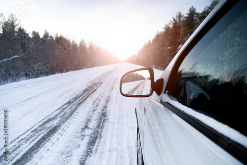 White car on a winter road through a snow covered forest.