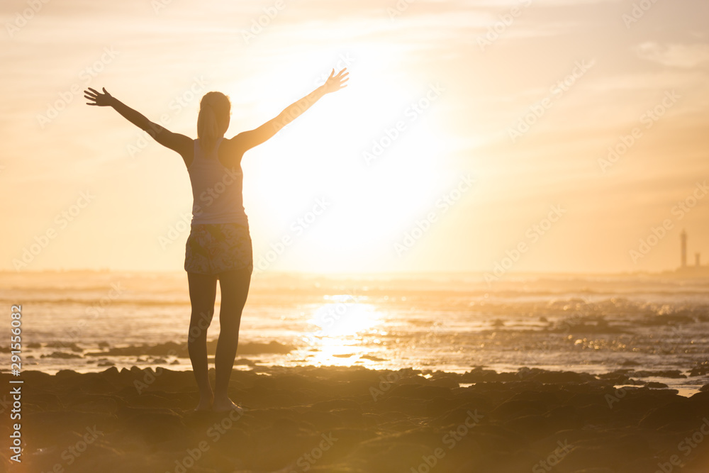Fototapeta Silhouette of free woman enjoying freedom feeling happy at beach at sunset. Serene relaxing woman in pure happiness and elated enjoyment with arms raised outstretched up.