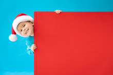 Happy Child Holding Red Christmas Banner Blank Against Blue Background