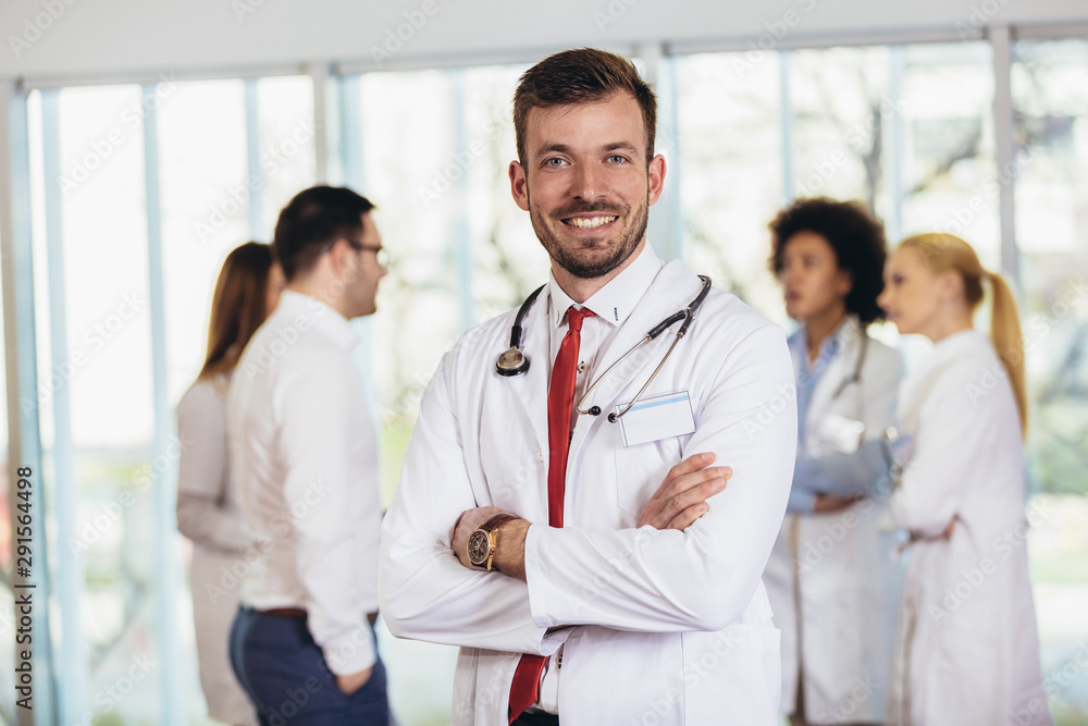 Fototapety, obrazy: Male doctor with colleagues in background, doctor looking at camera with emergency team in background