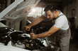 Mechanic is repairing an engine in the auto repair shop