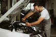 Male mechanic using socket wrench while working on car engine in a workshop